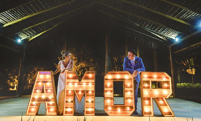 Casamento no campo de Thaís e Theo foto dos noivos no letreiro amor